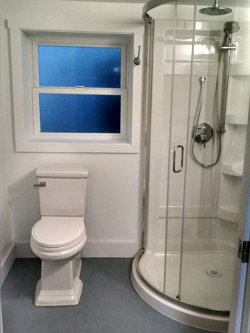 Cute Basement Bathroom - No more creaking up the stairs to use the bathroom.  This basement bathroom was built from scratch -- walled in and plumbed by AmyWorks.  It features a a pocket door, blue marmoleum floor and and a sweet corner shower.  Cute!
