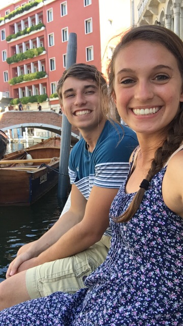 Kasey and his fiancee lounging beside a Venetian canal.