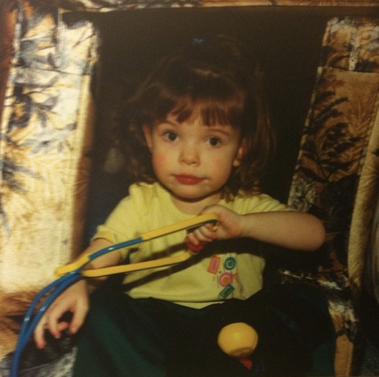 Lauren at approximately three years old, holding a toy stethoscope.