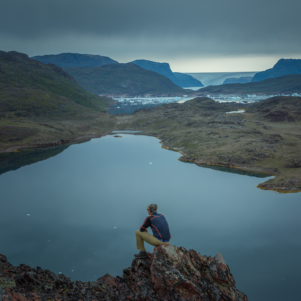 A traveller taking in the vista and feeling small next to the Tasiusaq lake in South Greenland, by Stacy William Head.jpg