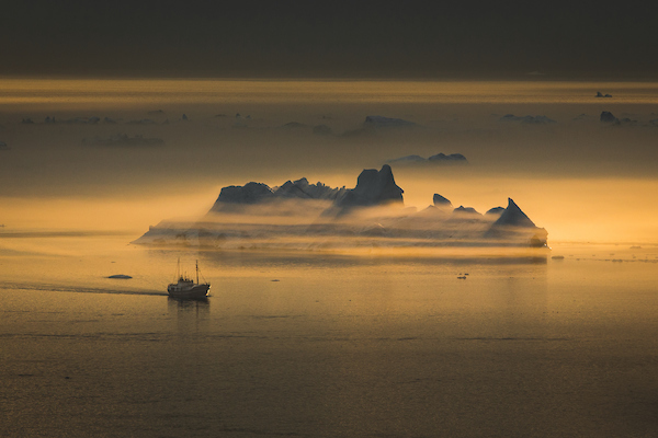 A fishing vessel passing an iceberg shrouded in fog near Ilulissat ice fjord in Greenland.jpg
