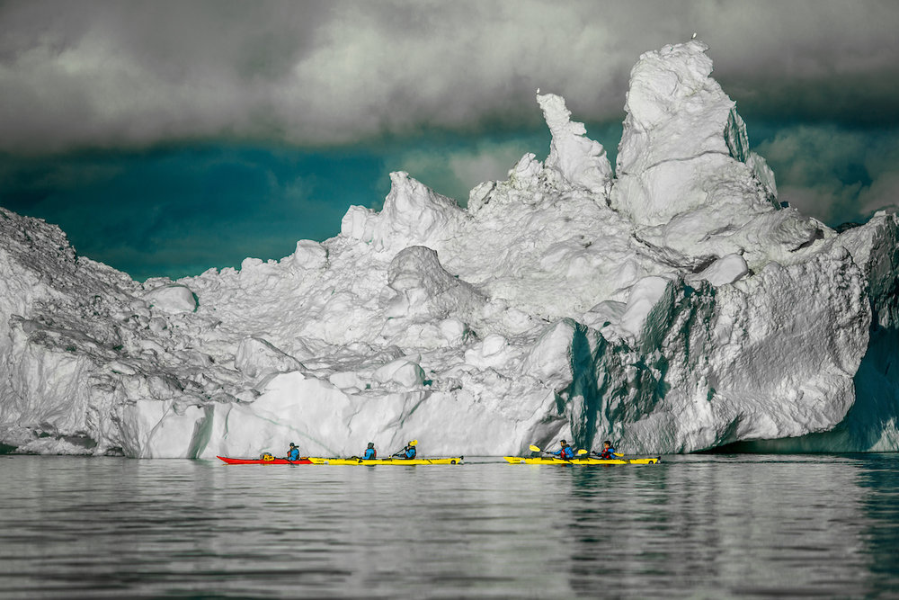 Small kayaks at safe distance paddling in front of a huge iceberg in the Disko Bay in Greenland.jpg