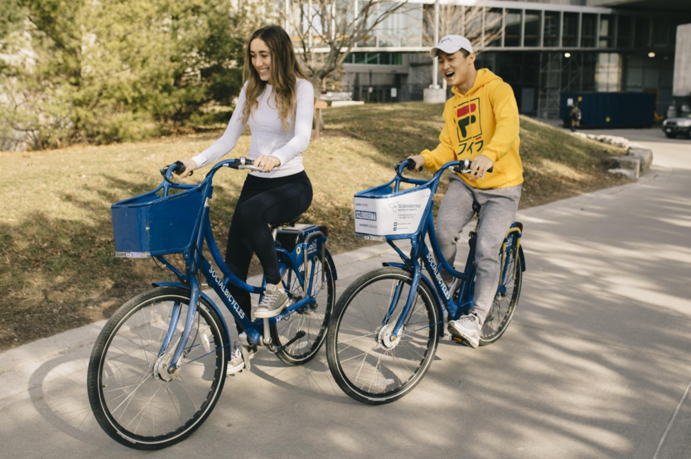 Students on the  SoBi  riding through McMaster Campus
