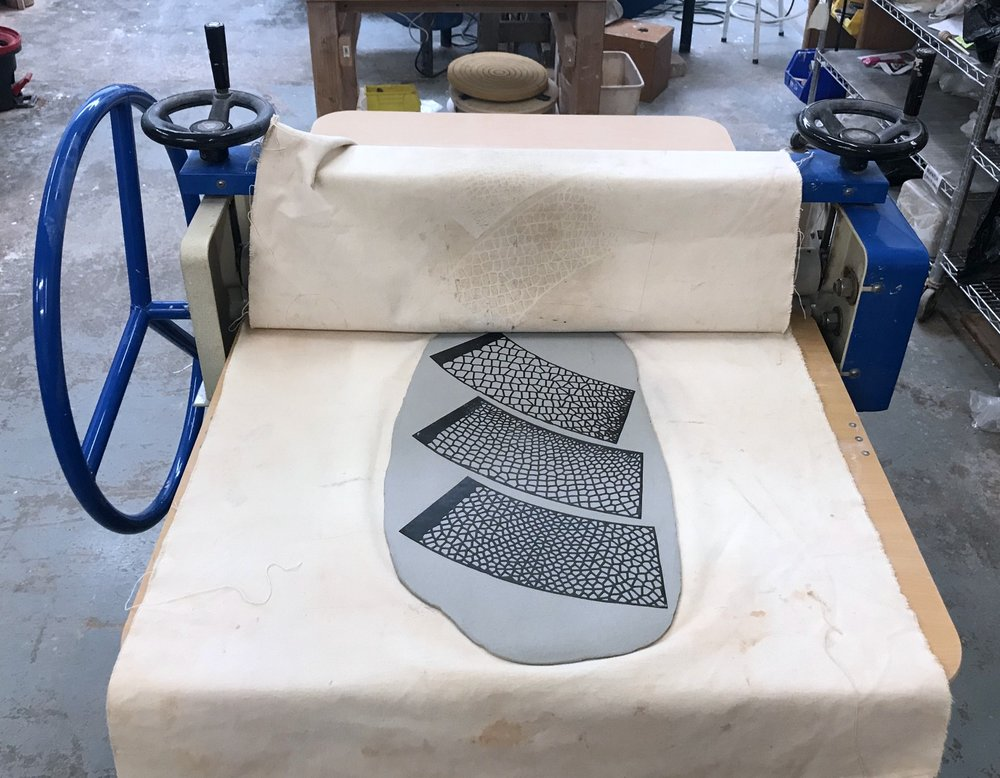 Pressing templates into a slab of clay with a slab roller.