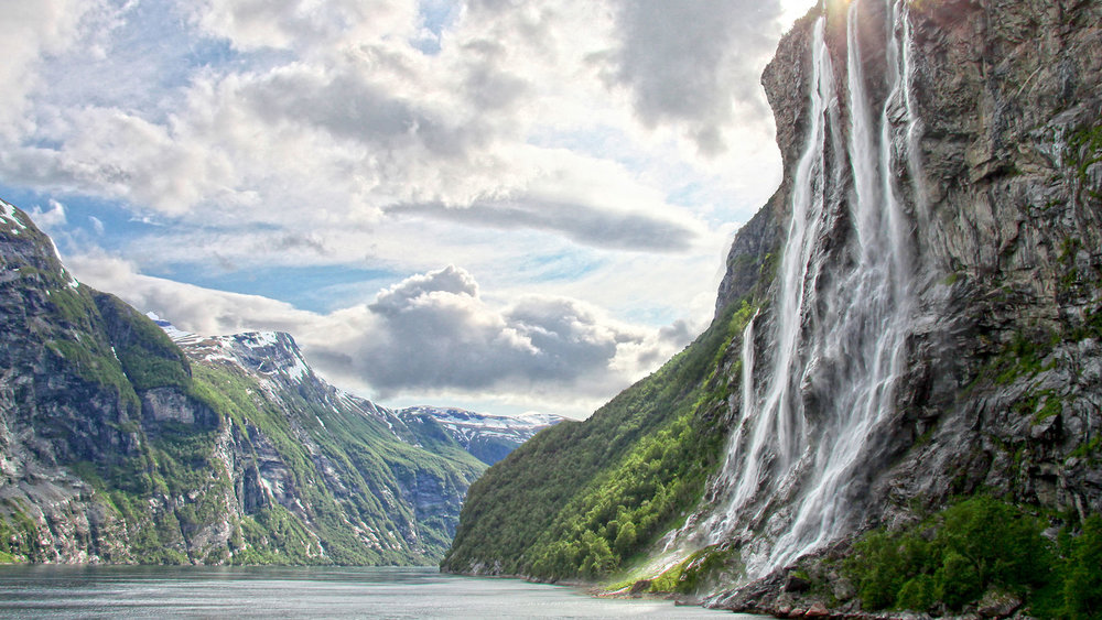 We'll sail monohull boats through deep blue fjords, past flowing waterfalls, under sharp, snow-capped mountains that tower high above. -