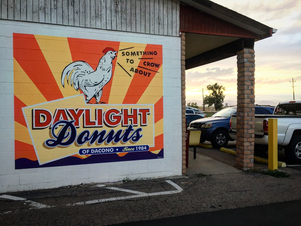 """OLD SCHOOL CHARM - While painting this mural for Daylight Donuts of Dacono, a man walked up and expressed his opinion on signs painted directly to brick. """"Signs now days just don't have the charm they used to."""" adding later, """"You can't fake this."""" The design of this mural was inspired by the current franchise logo mixed with a little media that's been on the iconic box of donuts for years."""