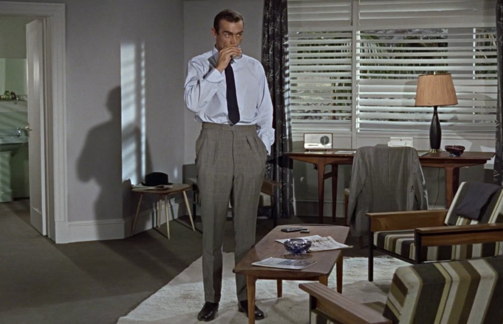 Sean Connery, as James Bond, wearing grey pleated trousers.