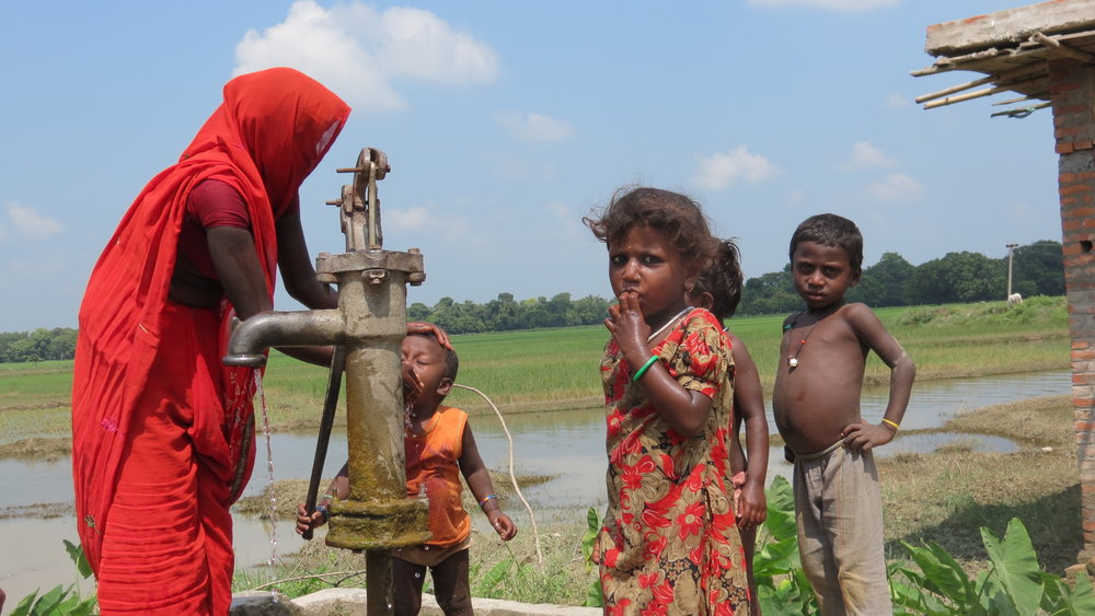 running water is not a luxury in homes here, so this mother brought her children to the local well to get a drink