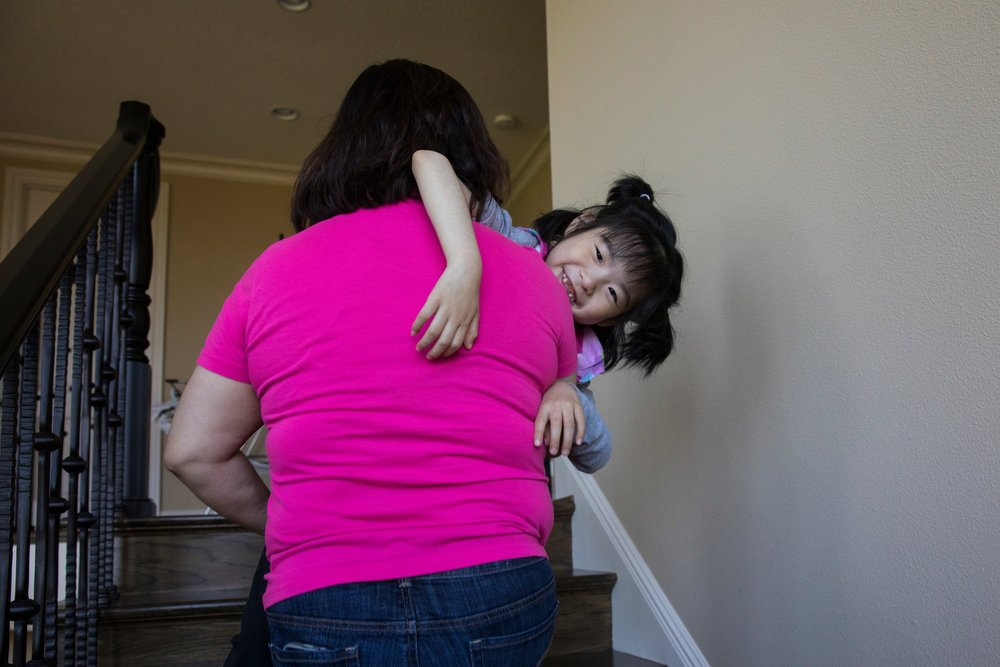As Yuna, in the arms of her caregiver, Anne Marie Nguyen, grows, it gets harder to carry her up and down the house's several flights of stairs.