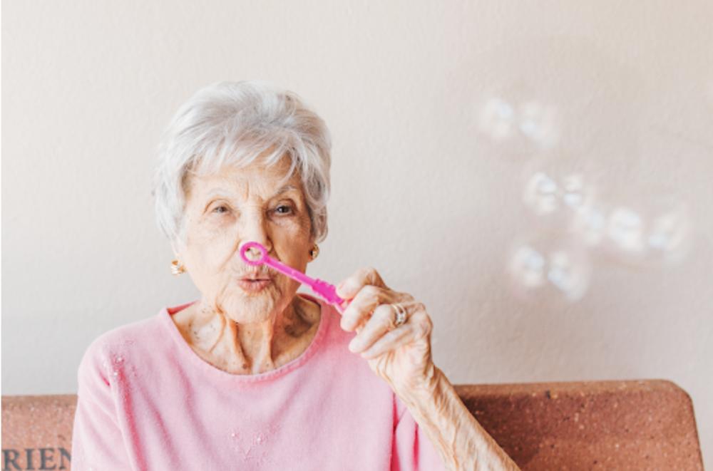 Elderly woman blowing bubbles.