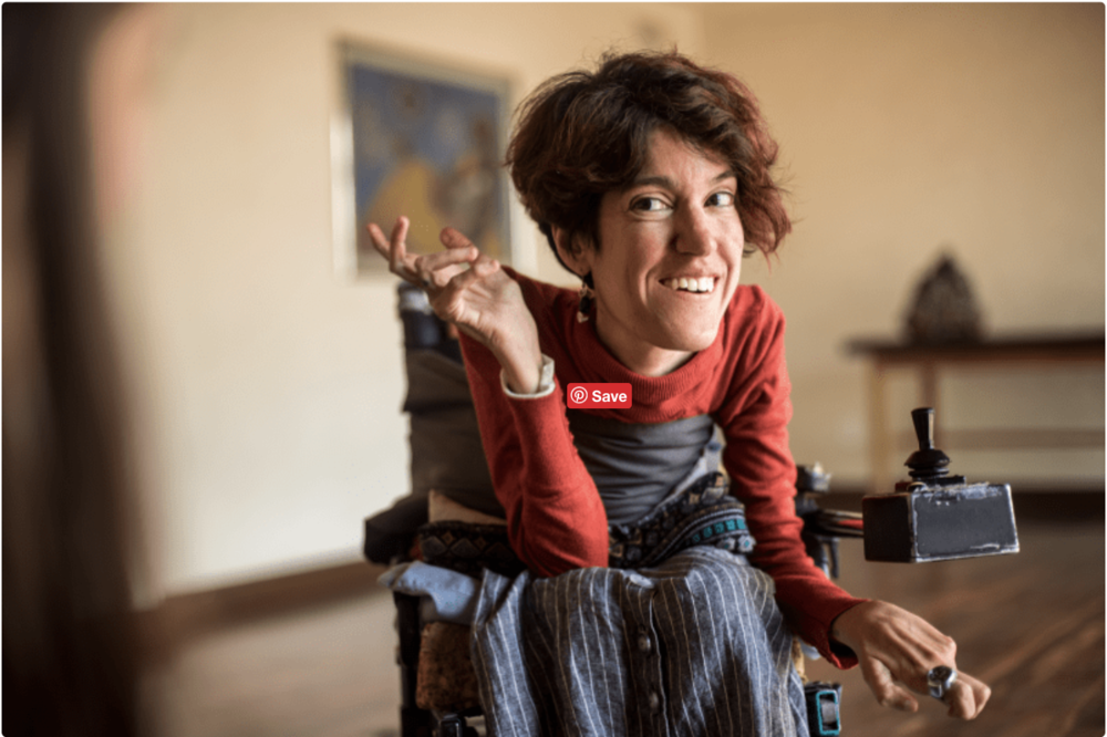 A woman with Spinal Muscular Atrophy in a wheelchair smiling.