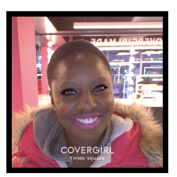Atima virtually trying on makeup using COVERGIRL's in-store technology.