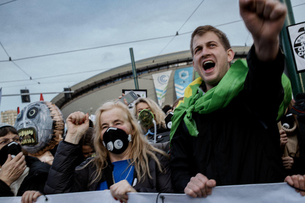 """Protesters shout """"wake up for the climate"""" next to the UN conference on climate change in Katowice."""