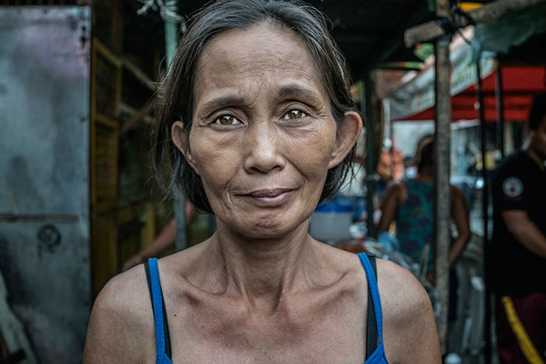 "Portrait of Lucia Abletes, mother of Junnar Abletes, 27, who was gunned down in Duterte's ""War on Drugs"" when he returned for a family visit from the island of Samar. Lucia did not believe it was safe for him to be in Market 3 slum, even though he had stopped using drugs. Her worries were confirmed. Junmar leaves behind a young son that she will now raise. Market 3 slum, Navotas, Metro Manila, Philippines"