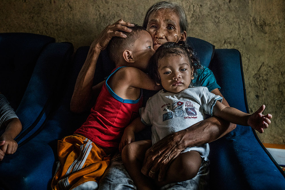 Remy Fernandez, 84 years old, holds her grandchildren that she is raising, there are seven in all, because her son, Constantino de Juan, a methampetamine user, was killed by masked men and the mother is in prison due to a drug arrest. The chair in which she sits has a hole in it after it passed through his body. Baby RJ was born in prison. Constantino, upon seeing the masked assassins, instructed CJ, five years old and wearing the red tank top, to take care of his siblings because he knew he was about to be assassinated. Payatas, Metro Manila, Philippines