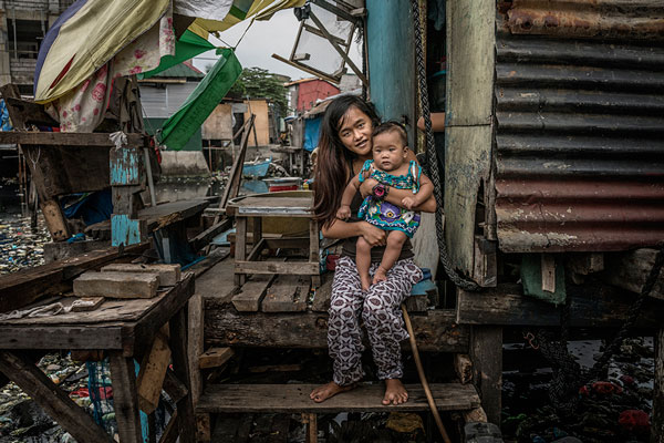"Jasmin Dorana, a 15 year old widow, holds her baby, Hazel, born just a month before her partner, John ""Toto"" Dela Cruz was pulled by his hair out onto this porch and shot four times in the head and in the chest. Bagung Bayan, C4, Navotas, Metro Manila, Philippines."