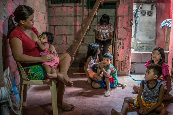 "Roda, 29 years old, and the 7 children for whom she is responsible, after her husband, Crisanto, a garbage picker at the massive dump site nearby, was killed in an extrajudicial killing as part of Duterte's ""War on Drug"". Roda cannot work because she has a ulcerous infection on her thigh and she also needs to look after the children. Some of the older children are sent out to sell fried banana and other food on the street to bring in a little cash. Payatas, Metro Manila, Philippines."
