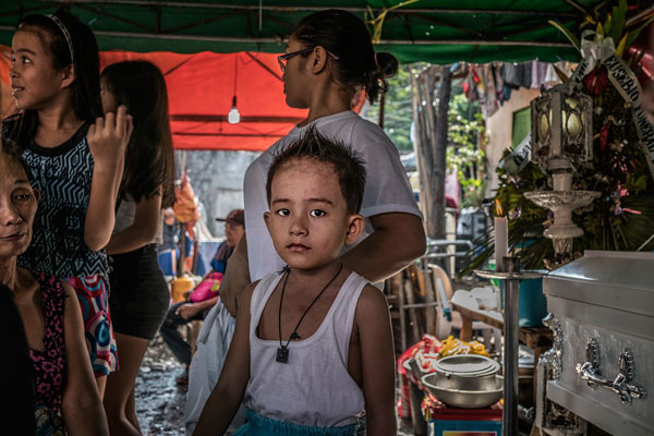 Son of Junmar Abletes at his father's wake overlooked with a worried glance by his grandmother. Market 3 slum, Navotas, Metro Manila, Philippines.
