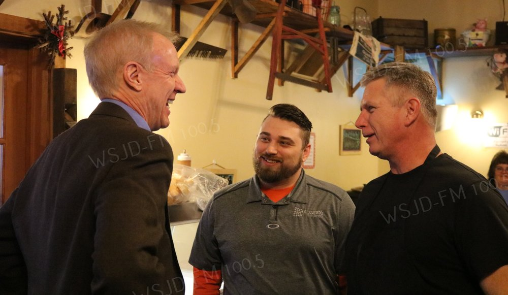 Governor Bruce Rauner (L) chats with Hogg Heaven BBQ owner Rick Marshall (R) and his son Robert during a lunch time stop in Mt. Carmel Thursday.