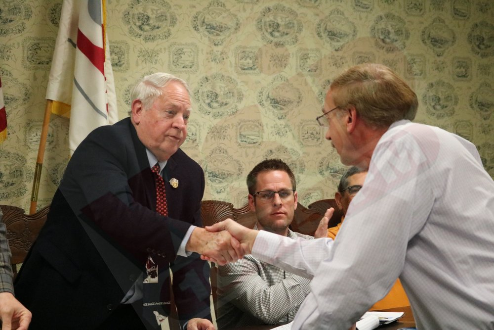 Mayor Bill Hudson shakes hands with Tony Hodgson of Heartland Worship Center after he presented a check for the continued operation of the Senior Citizens Center.