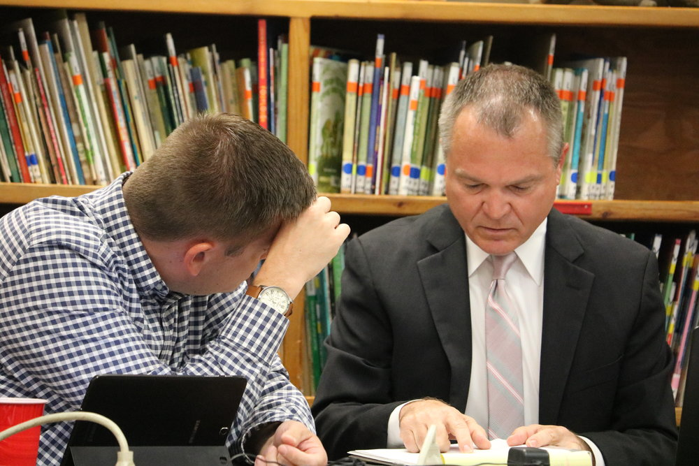 School Board member Kyle Peach (L) confers with District #348 Superintendent Dr. Chuck Bleyer prior to Monday's board meeting.