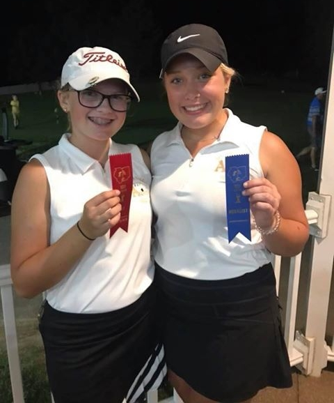 Daisy Schrader (L) & Allyson Armstrong show off their 2nd and 1st places ribbons from the Big 8 girls golf tournament.
