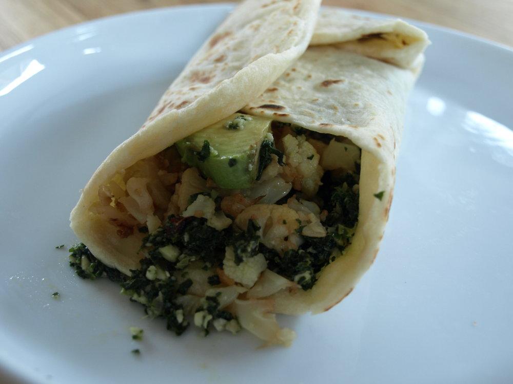 A wrap of mustard green pesto, roasted cauliflower and sliced avocado.