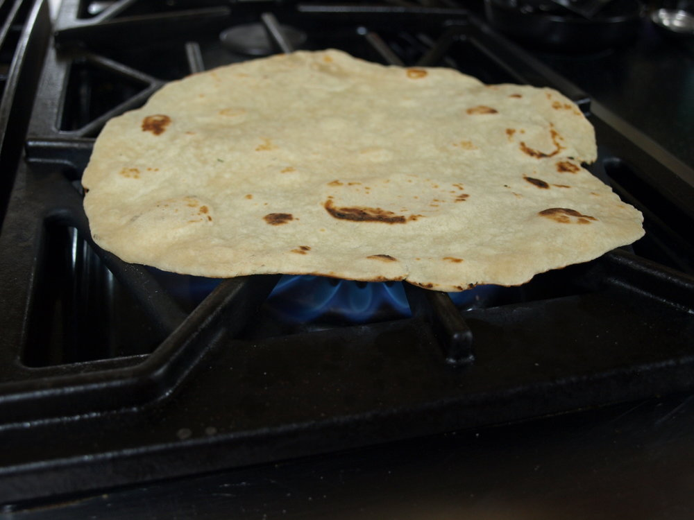 Reheat leftover tortillas on a flame.