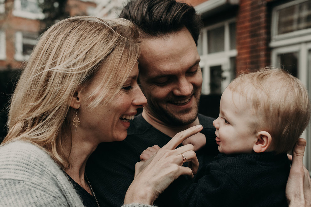 Mom, dad, and baby all smiling at eachother in ROtterdam, The Netherlands. OUtside in their garden with lots of diffused light