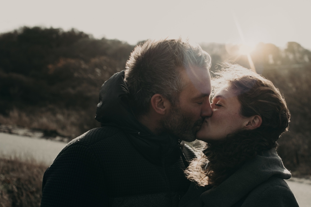 Man and woman kissing at the beach in den haag. with a sun flare perfectly behind them