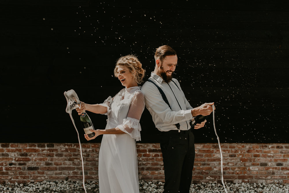 Bride and groom popping champagne in rotterdam, The netherlands after getting married. They are happy and smiling up against a black wall in direct sunlight