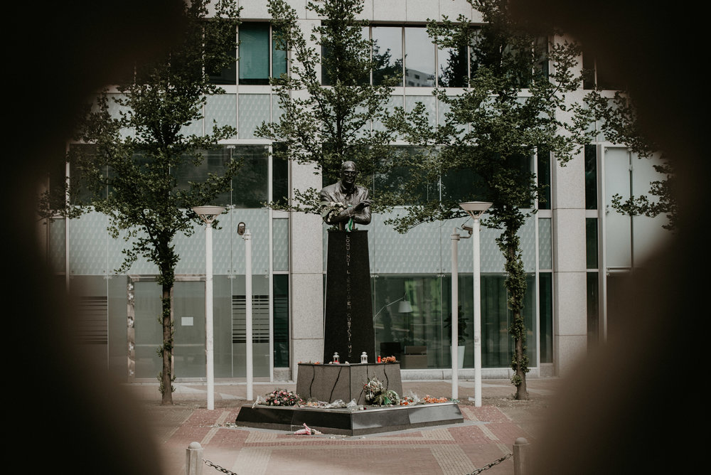 Statue of Pim Fortuyn in Rotterdam Center with flowers all around.