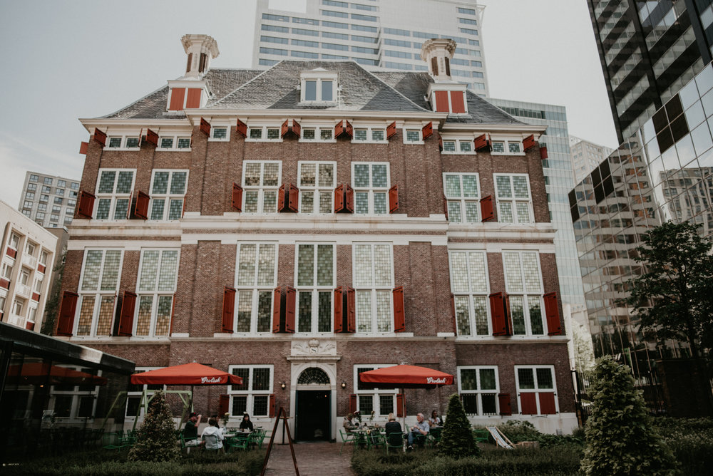 Rotterdam expat center back garden. an old historic building with white and red trim and people eating at the bottom at the cafe there.