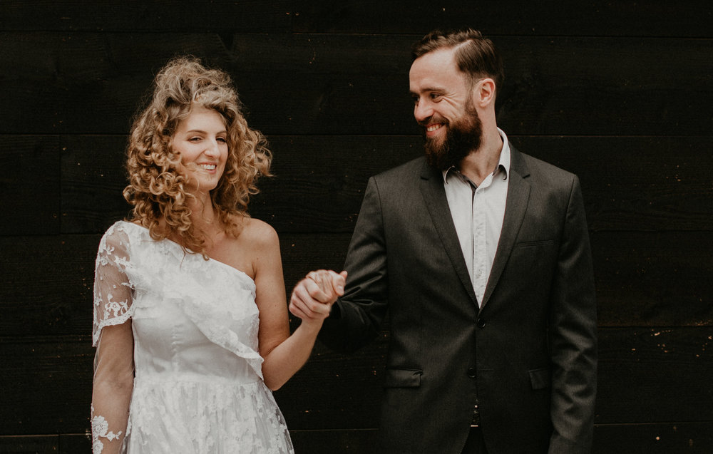 Bride and groom aginst a black wall looking lovingly at eachother laughing. photos by 51north photography