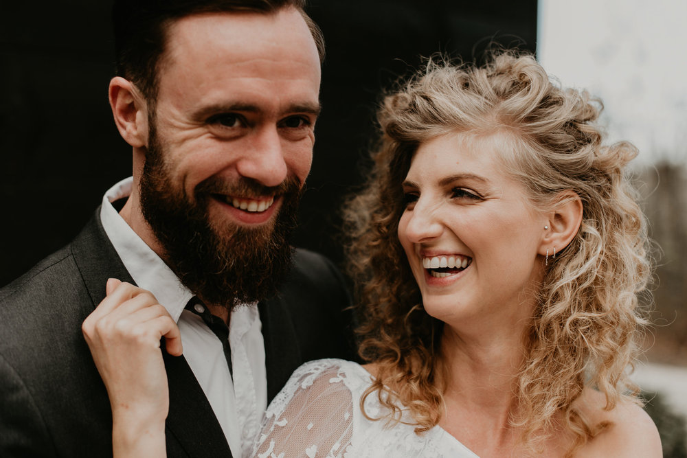 bride and groom smiling and laughing looking into the distance with huge smiles aginst a black wall. Photos by 51Northphotography