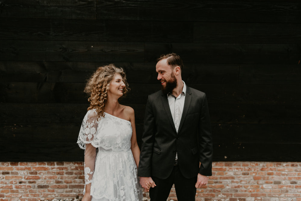 bride and groom agist a black wall with huge smiles looking at eachother in their wedding clothes. Photos my 51North photogrphy