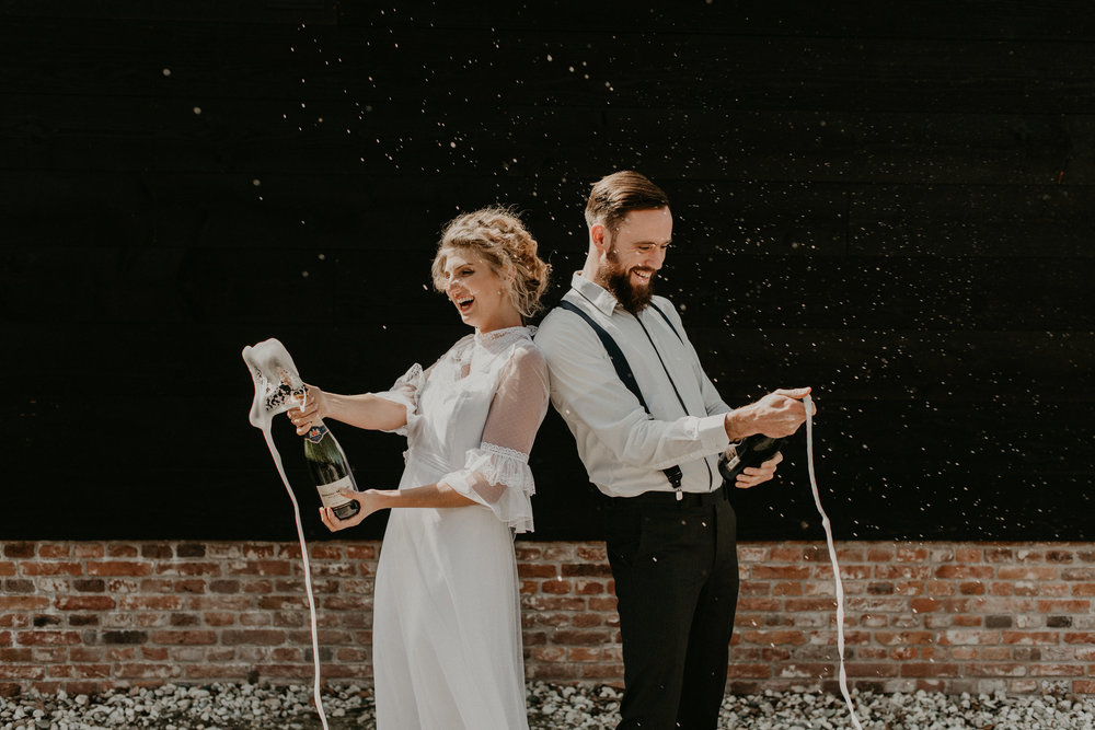 Bride and groom popping spraying champagne bottles. Photos by 51north photography