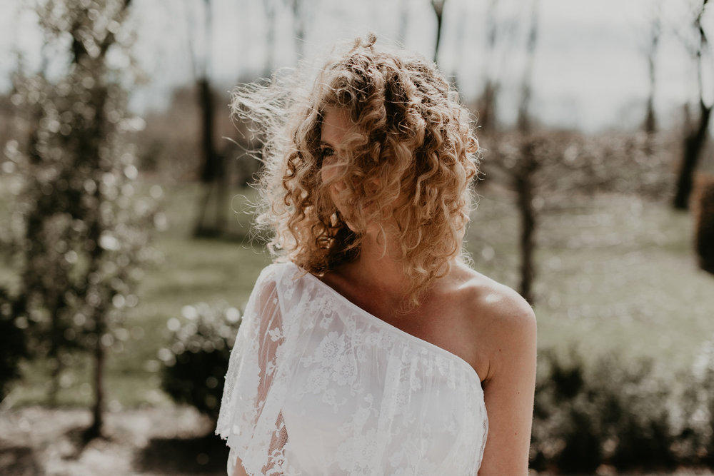 bride standing alone with the wind in her hair flying in front oher face. photos by 51north photography