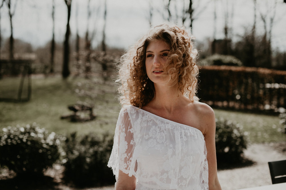 Photo of a bride standing alone with the wind in her curly blond hair. photos by 51north photography