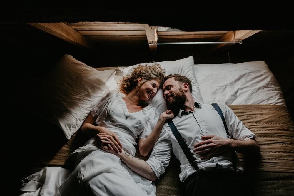 bride and groom laying on a bed in a dark attic smiling and laughing together. photos by 51North Photography