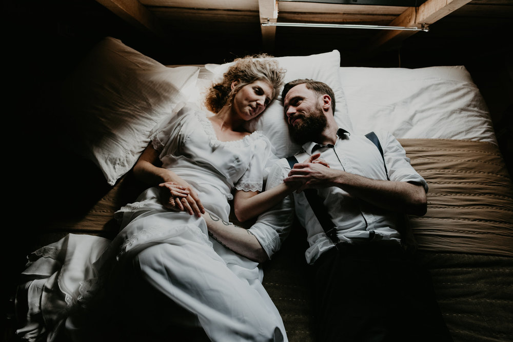 bride and groom laying together in a dark attic on a bed. photos by 51north photography