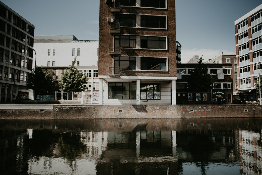 Image of a rotterdam canal with an abandoned building next to it