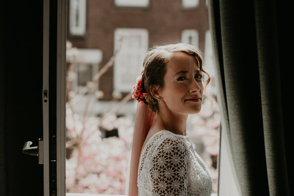 Rotterdam bride looking right into the camera with a little smile while sitting in a window