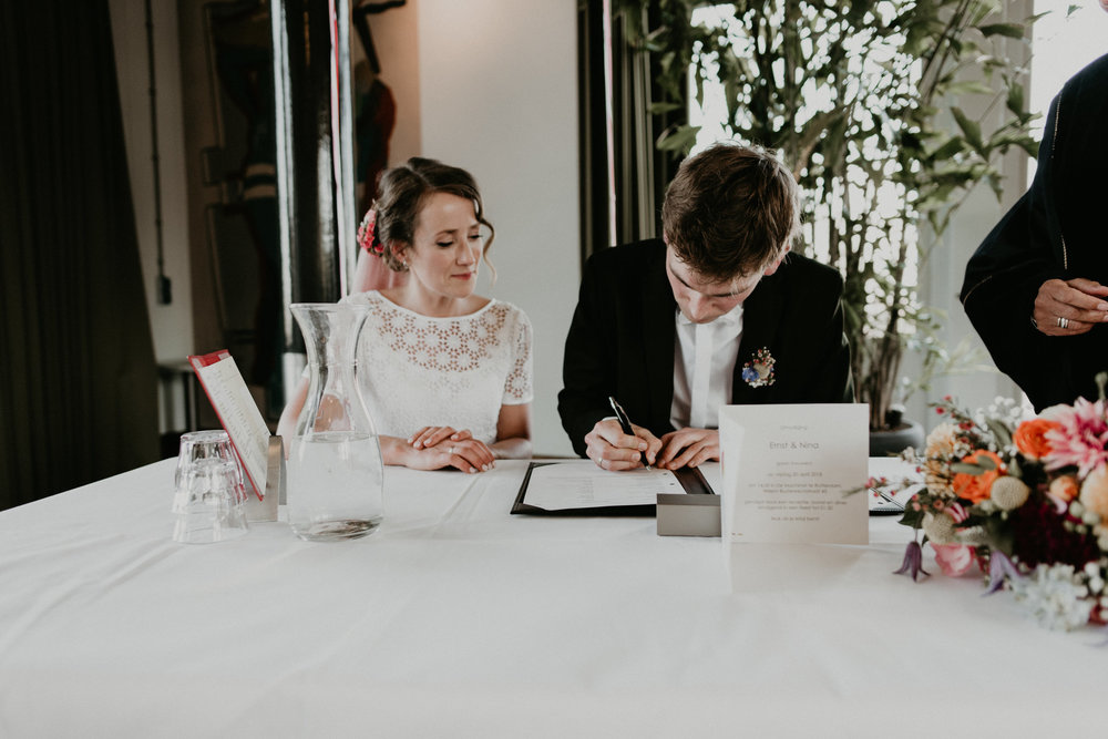 Bride and groom signing their marriage license at de machinist in Rotterdam, NL