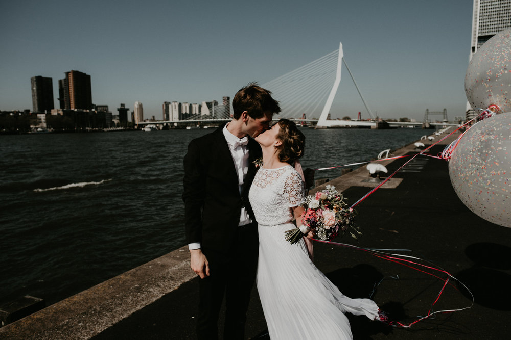Bride and groom standing with the erasmus brug in the background.