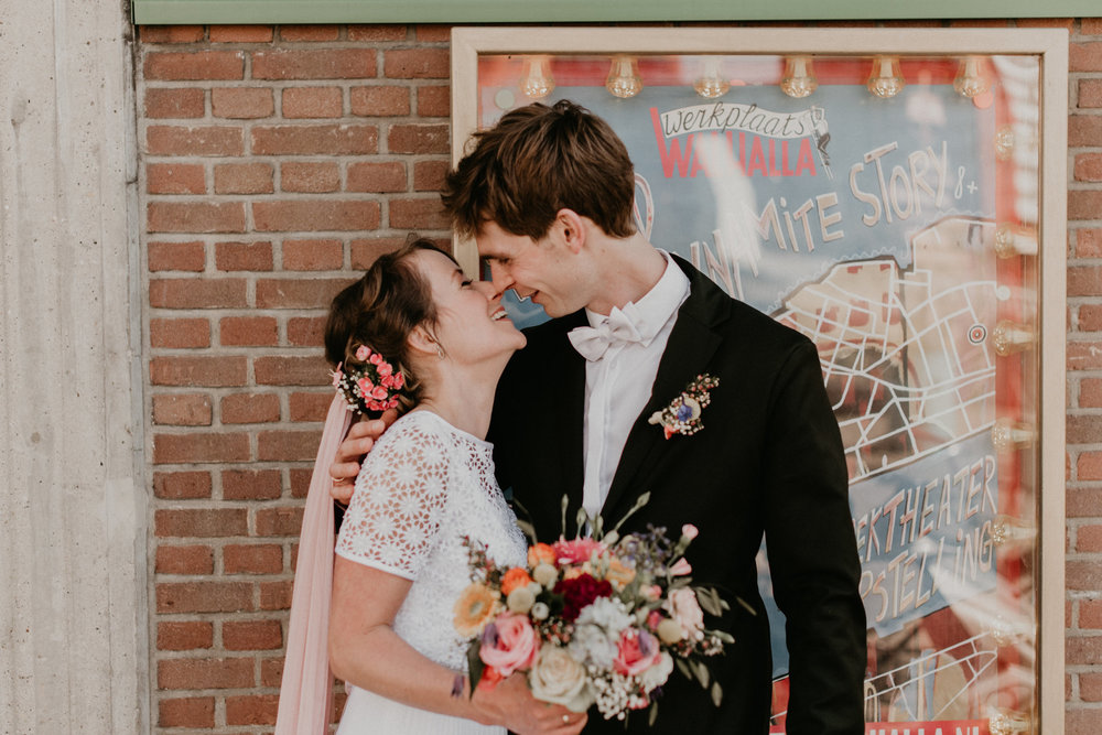 bride and groom standing in froming of a movie poster at de Walhalla in rotterdam Nederlan