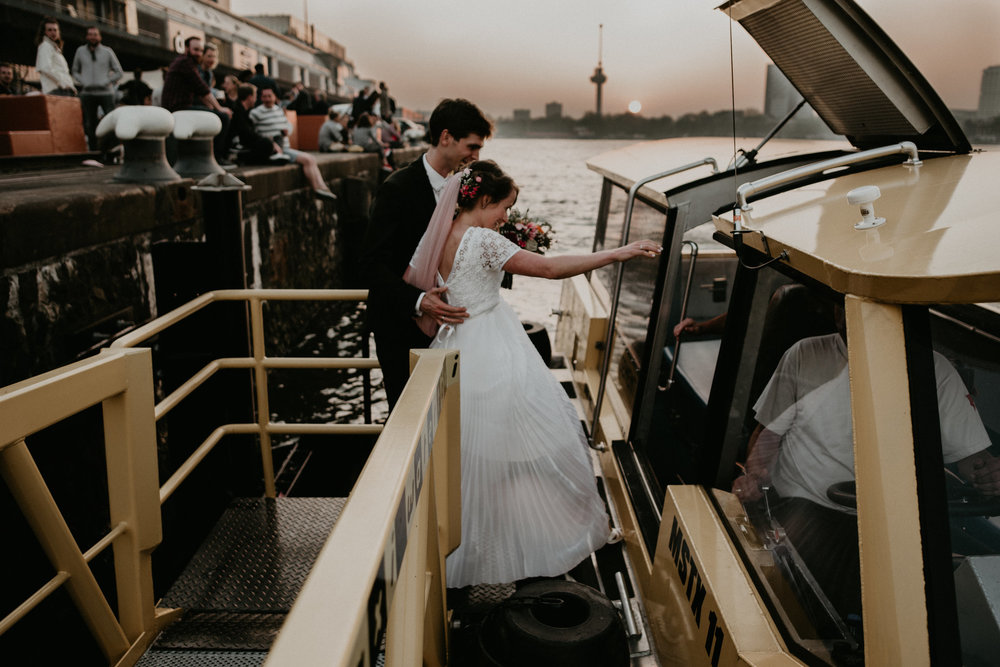 bride and groom getting into the rotterdam water taxi at sunset