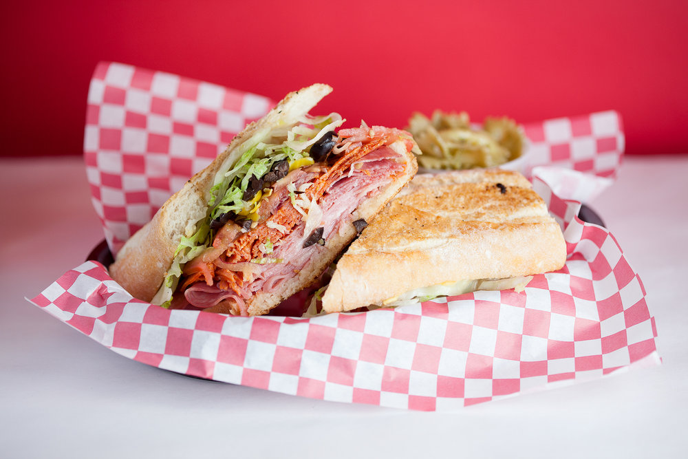 The Italian Job - Genoa salami, mortadella, pepperoni, hardwood smoked provolone cheese, Pearl Bakery French baguette, tomato, lettuce, red onions, pepperoncini, olives, dijon, and balsamic marsala vinaigrette. Comes with one free side. (Gluten-Free bread available)10.75/14.75