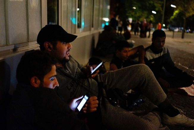 GettyImages-migrants-with-phones.jpg.653x0_q80_crop-smart.jpg