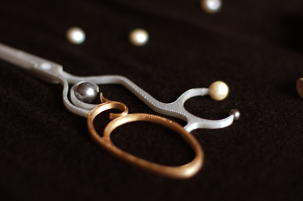 Scissors - A scissor is like an accessory for the craftsman. Pearls, which symbols beauty and innocence, are used to salute the craftsman and artisan. It is more about the spirits than simply tools.